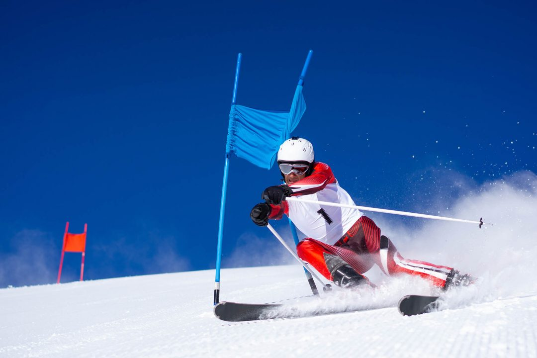 aggressive motivated focused concentrated ski racer man skiing super g touching pole goal on sunny winter day with clear blue sky