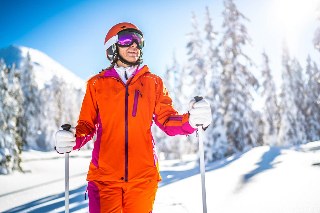 medium shot happy female skier woman standing in deep snow trees mountain on sunny winter day